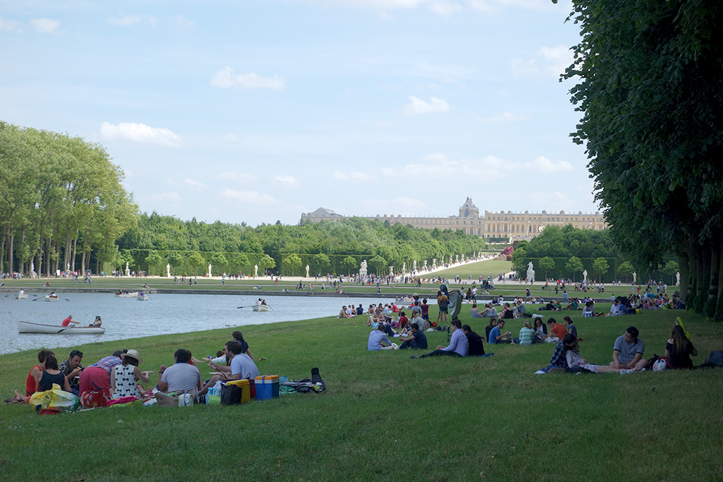 Visitors picnicking on the lawn at Versailles