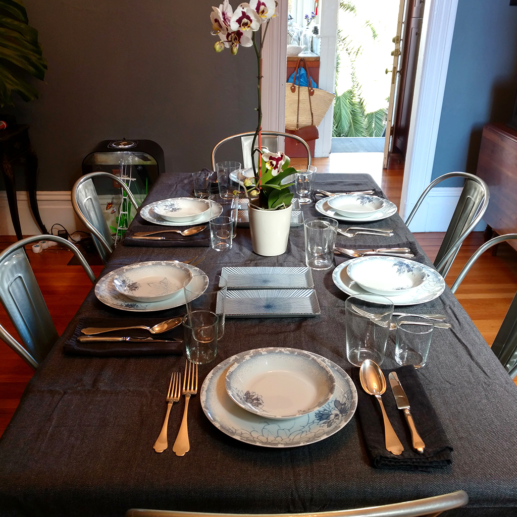 Gray tablecloth and blue china with black napkins